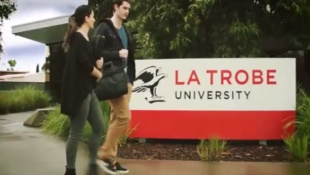 Two students walking in front of the La Trobe University sign